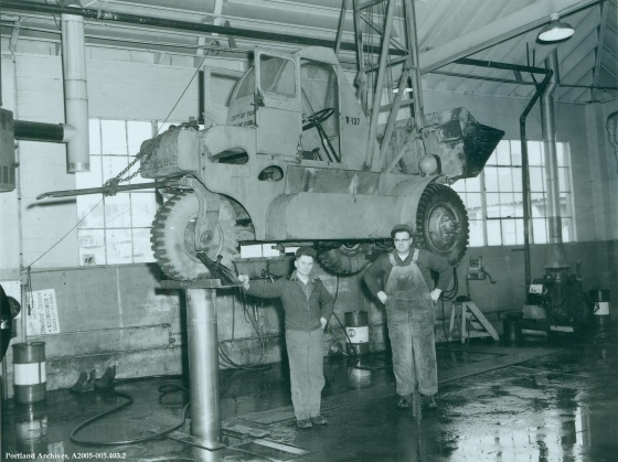 Two men with front loader on lift at Stanton Yard, circa 1955: A2005-005.403.2