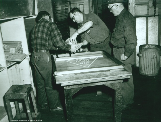 Three men printing signs in sign traffic shop