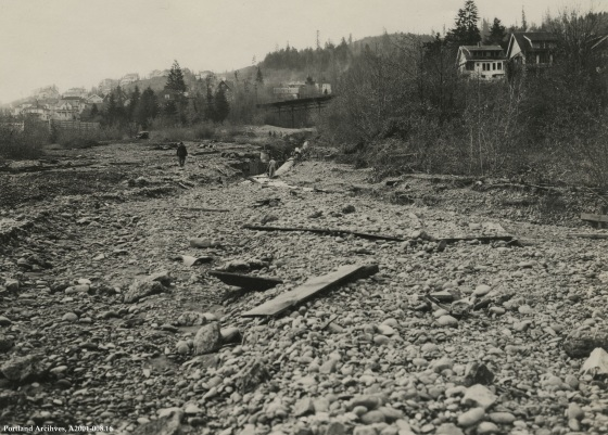 Balch Gulch Trunk Sewer  looking upstream from rocky field below sewer intake with view of bridge and houses, February 28, 1922: A2001-008.16