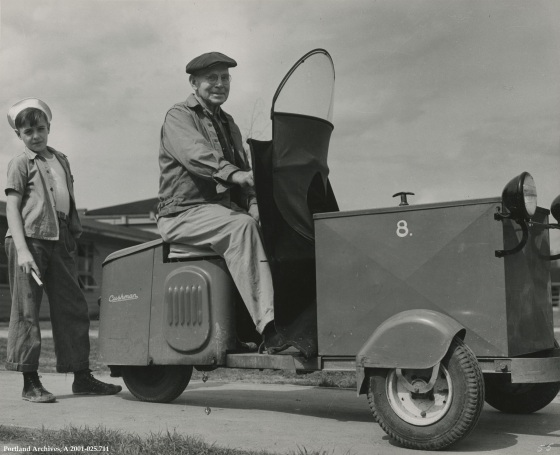 Man sitting a the vehicle used for Vanport maintenance with boy standing behind, circa 1944: A2001-025.711